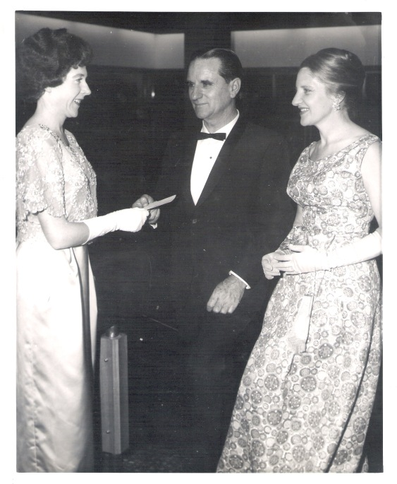 Wollongong Council Civic Ball celebrating opening of new town hall, Helga Burnett as usher taking entrée cards from guests Dolph Murray, principal Librarian Wollongong City Library and Mrs. Murray